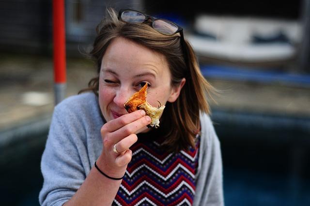 Portrait d'une femme mangeant une pizza